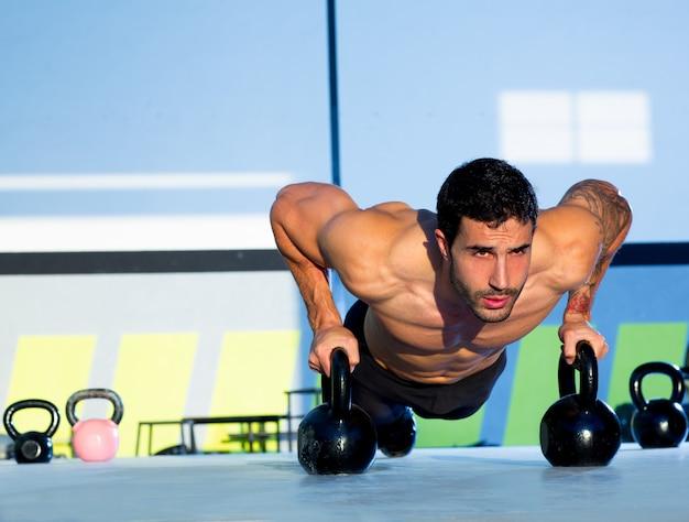 Gym man push-up strength pushup with kettlebell Premium Photo