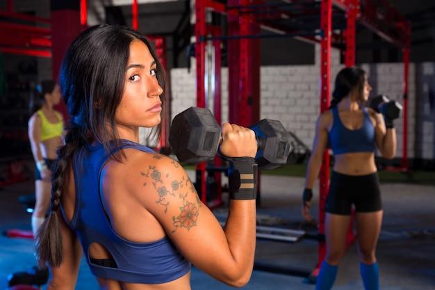 ヘックスバーベルトレーニングのジム女性 Premium写真