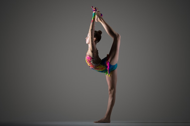 Gymnast girl doing standing backbend with mace Free Photo