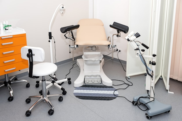 Gynecological cabinet with chair and other medical equipment in modern clinic Premium Photo