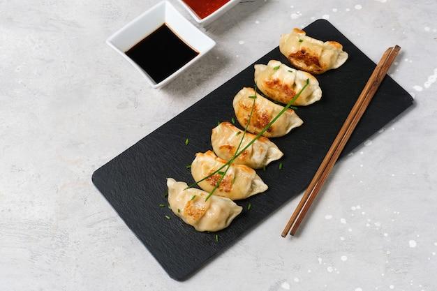 餃子醤油餃子。アジア料理。典型的な食べ物日本、中国、韓国。配達の持ち帰り Premium写真