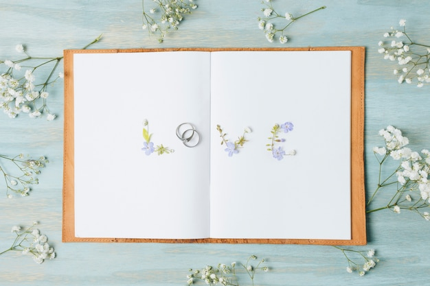 Gypsophila flower around the love text on white page book over the wooden desk Free Photo