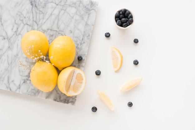 Gypsophila flower with lemons and blueberries on white background Free Photo
