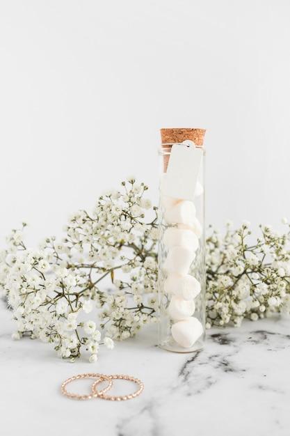 라든지 꽃; 결혼 반지와 흰색 배경에 테스트 튜브에 마시 멜로 무료 사진