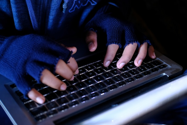 Hacker hand stealing data from laptop top down. Premium Photo