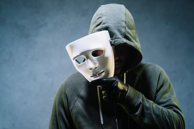 Hacker holding mask Free Photo