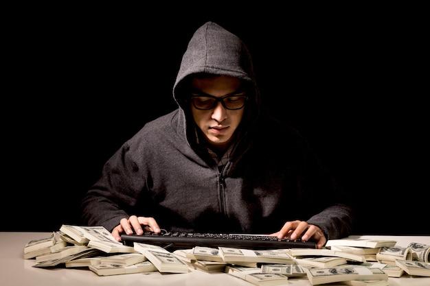 Hacker in a hood stealing information with computer on dark background Premium Photo