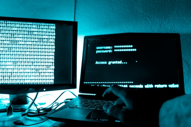 ハッカーはラップトップのキーボードにコードを印刷して秘密の組織システムに侵入します。 Premium写真