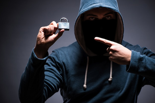 Hacker wearing hood in dark room Premium Photo