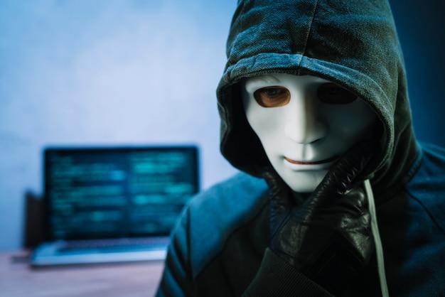 ラップトップの前でマスクを持つハッカー 無料写真