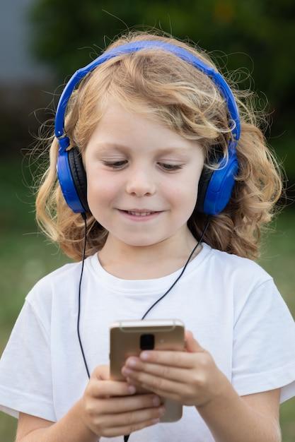 青いhadphonesと携帯電話で音楽を聞いて長い髪の面白い子 Premium写真