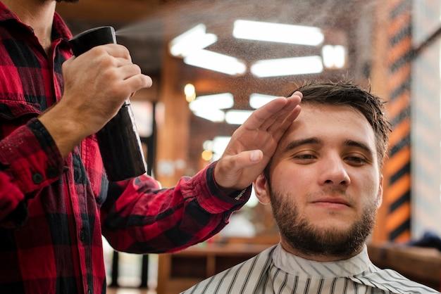 Haidresser spraying the client hair Free Photo