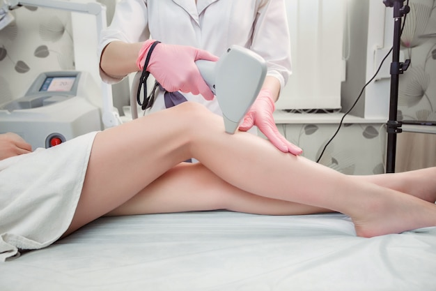 Hair removal cosmetology procedure from a therapist Premium Photo