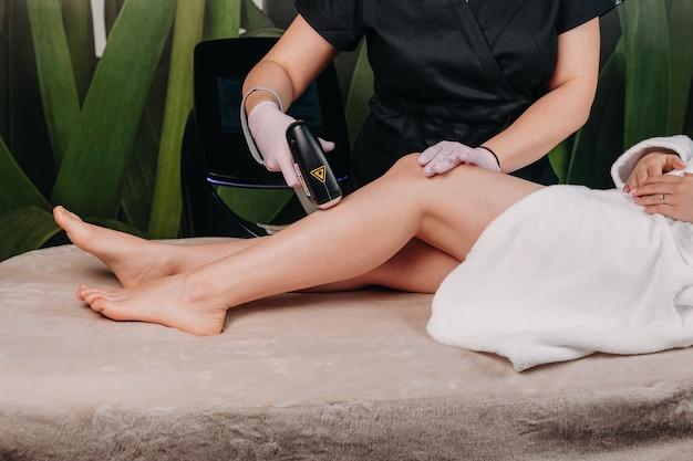 Лазерная эпиляция на ноге, которую проводит внимательный дерматолог в спа-салоне. Premium Фотографии