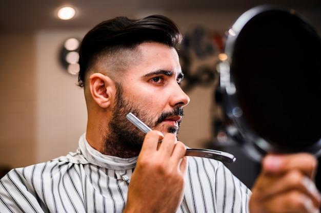 Hair salon costumer looking in the mirror Free Photo