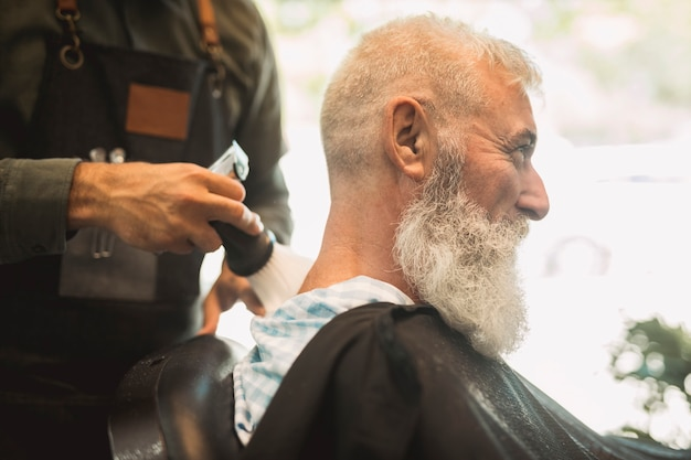 Hair stylist correcting haircut in salon Free Photo