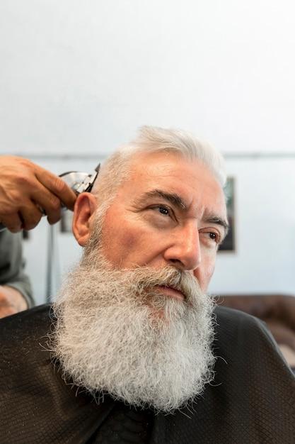 Hair stylist cutting hair to elderly man in barber shop Free Photo