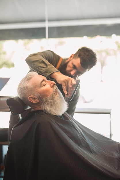 Hair stylist trimming beard to aged male in salon Free Photo