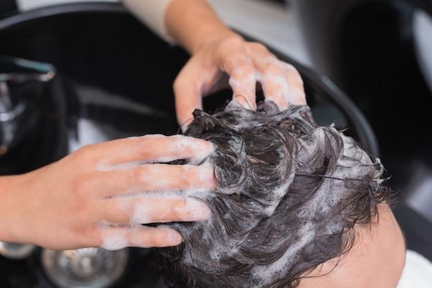 Hair stylist washing mans hair Premium Photo