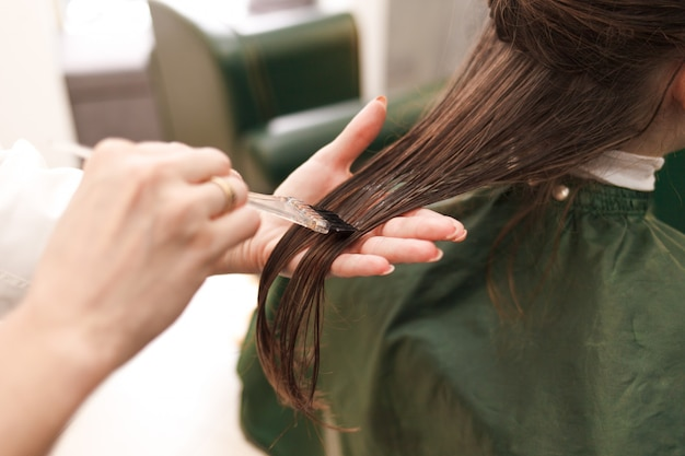 Hairdresser applies a hair mask to the woman in the beauty salon. botox and keratin hair straightening procedure Premium Photo