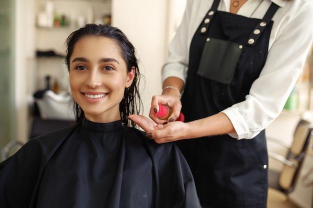 미용사는 여성의 머리카락, 정면도, 미용실에 무스를 적용합니다. 헤어 살롱의 스타일리스트와 클라이언트. 뷰티 사업, 전문 서비스 프리미엄 사진