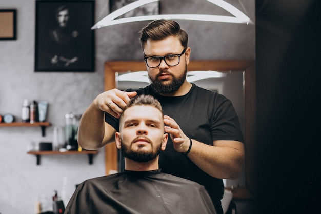 Hairdresser at a barber shop styling hair of a client Free Photo