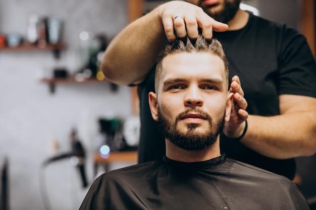 Parrucchiere in un negozio di barbiere che disegna i capelli di un cliente Foto Gratuite
