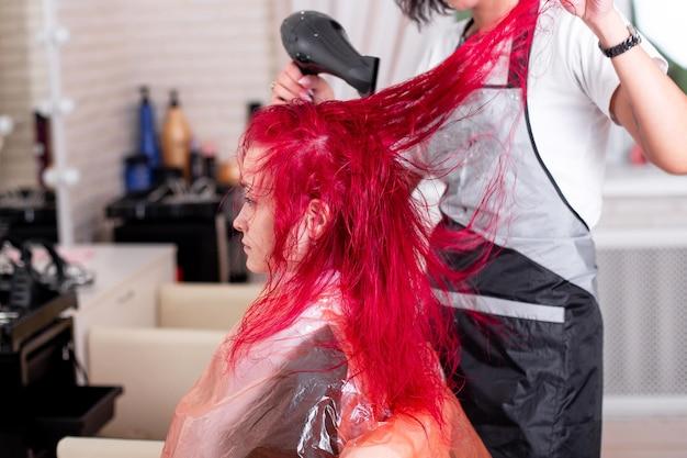 Hairdresser brushing and blow drying pink hair Premium Photo