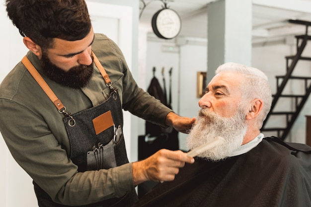 Hairdresser combing beard of aged client in barbershop Free Photo