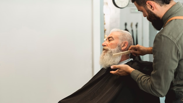 Hairdresser combing beard to senior client in salon Free Photo