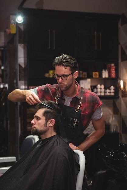 Парикмахер расчесывает волосы клиентов Бесплатные Фотографии