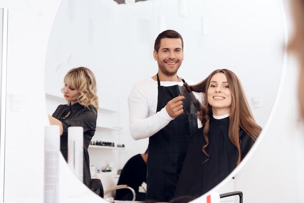 Hairdresser curling dark brown hair of beautiful woman. Premium Photo