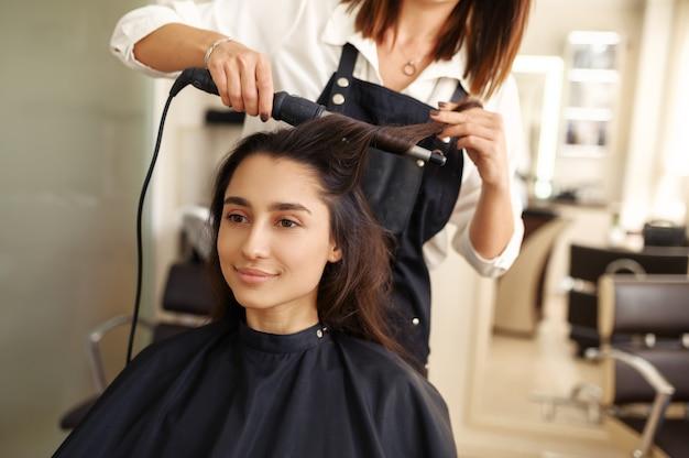 미용사는 여자의 머리카락, 미용실을 컬합니다. 헤어 살롱의 스타일리스트와 클라이언트. 뷰티 사업, 전문 서비스 프리미엄 사진