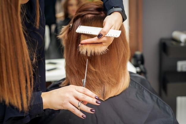 Парикмахер режет кончики рыжих волос, держа прядь рыжих волос между пальцами в салоне красоты. избавляемся от секущихся кончиков Premium Фотографии