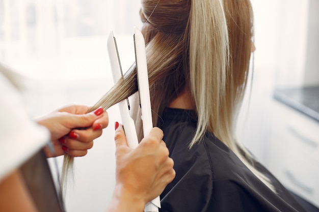 Hairdresser does hairstyle for her client Free Photo