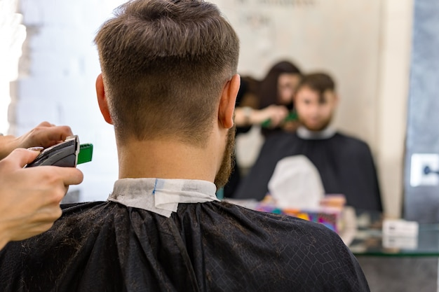 Hairdresser doing haircut for male client, man with beard using professional hairdresser tools, Premium Photo