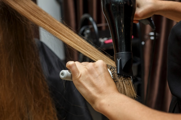 The hairdresser dries hair to the client with a hairdryer. Premium Photo