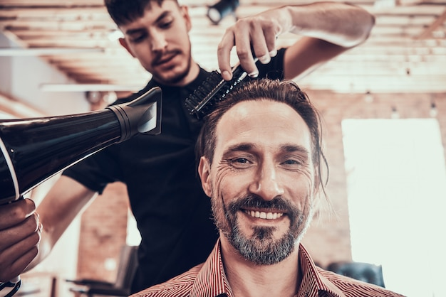 Hairdresser dries the hair to the customer after shearing Premium Photo