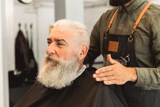 Hairdresser evaluating senior client in barbershop Free Photo