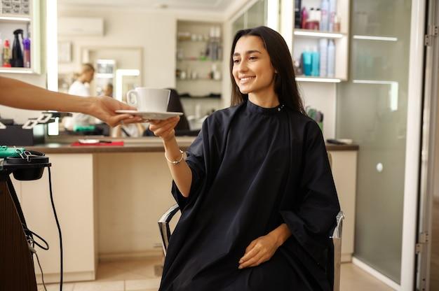 미용사는 여성 고객, 미용실에 커피 한잔을 제공합니다. 헤어 살롱의 스타일리스트와 클라이언트. 뷰티 사업, 전문 서비스 프리미엄 사진