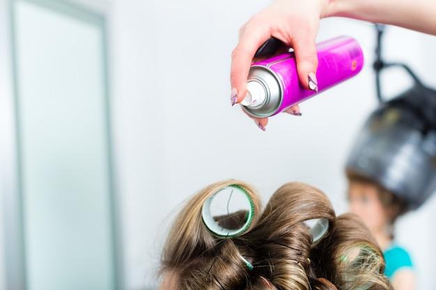 Hairdresser - hair stylist curling hairs Premium Photo