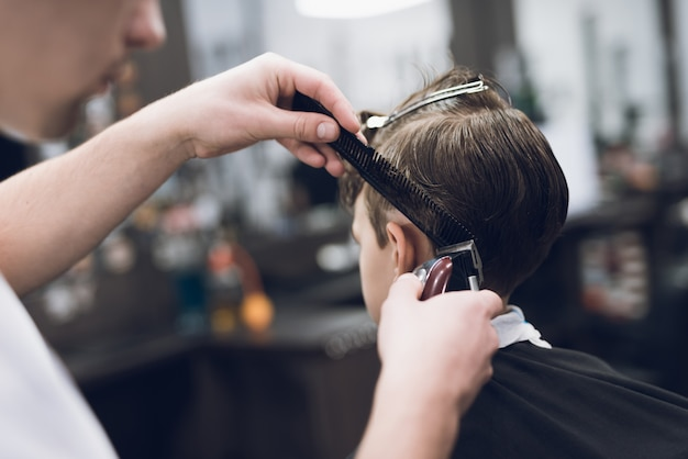 Hairdresser makes fashionable pretty hairstyle for the boy. Premium Photo