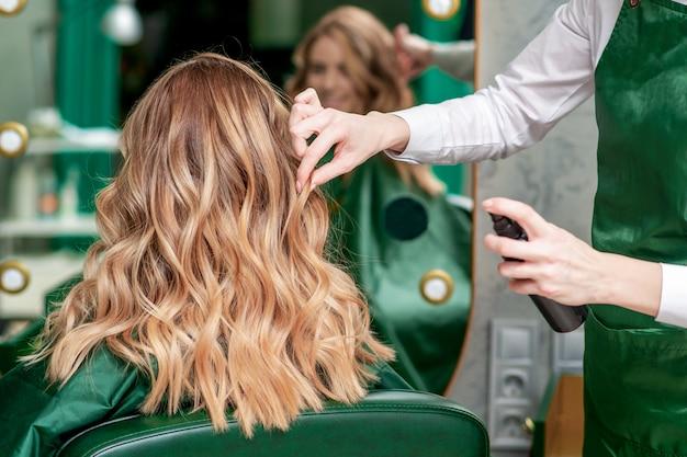 Hairdresser makes hairstyle. Premium Photo