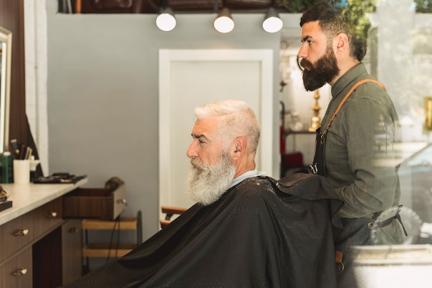 Hairdresser preparing for haircut bearded elderly client Free Photo