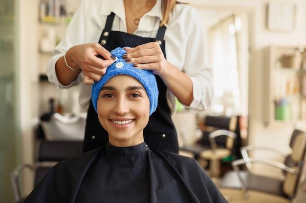 미용사는 여자의 머리, 정면도, 미용실에 수건을 넣습니다. 헤어 살롱의 스타일리스트와 클라이언트. 뷰티 사업, 전문 서비스 프리미엄 사진