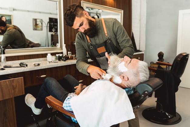 Hairdresser putting shaving cream to elderly client in beauty salon Free Photo