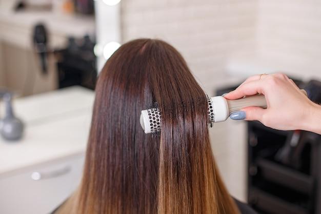 Hairdresser's hand brushing long brunette hair in beauty salon Premium Photo