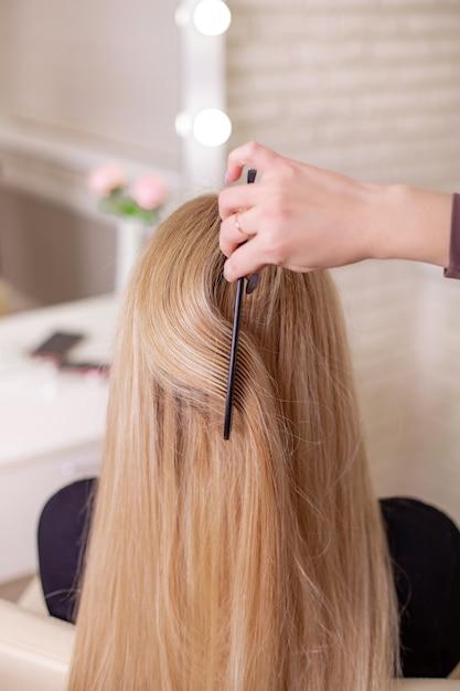 Hairdresser's hand brushing long natural blonde hair in beauty salon Premium Photo