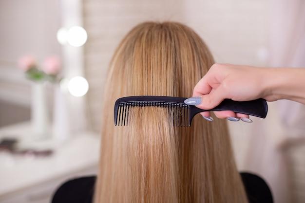 Hairdresser's hand brushing long natural blonde hair Premium Photo