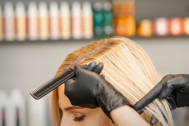 Hairdresser's hand combs female hair before dyeing in a beauty salon Premium Photo